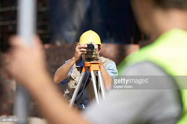 Surveyor Looking Through a Theodolite
