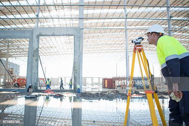 Surveyor using tripod and level on construction site