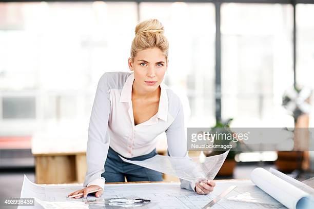 Landvermesser mit Blueprint auf Schreibtisch In Büro