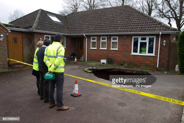 Surveyors at the home of Phil and Liz Conran in Main Road Walter's Ash High Wycombe Buckinghamshire after a 30ftdeep sinkhole opened up in the...
