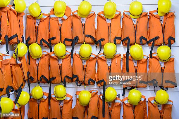 Survival equipment of orange lifejackets and yellow hardhats hanging on wall in nautical training class