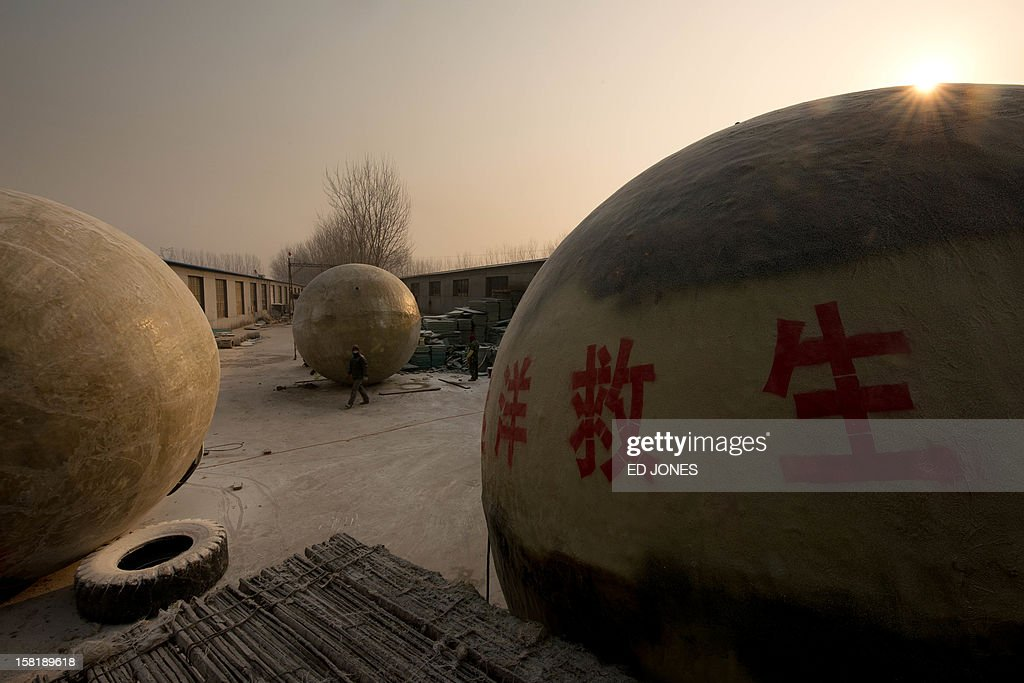 Survival pods dubbed 'Noah's Arc' by their creator, farmer Liu Qiyuan, stand in a yard at his home in the village of Qiantun, Hebei province, south of Beijing on December 11, 2012. Inspired by the apocalyptic Hollywood movie '2012' and the 2004 Asian tsunami, Liu hopes that his creations consisting of a fibreglass shell around a steel frame will be adopted by government departments and international organisations for use in the event of tsunamis and earthquakes. Liu has built seven pods which are able to float on water, some of which have their own propulsion. The airtight spheres with varying interiors contain oxygen tanks and seatbelts with space for around 14 people, and are designed to remain upright when in water. AFP PHOTO / Ed Jones