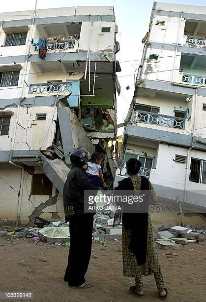 Surviving residents look at the broken building in the Gujarat town of Bhuj 29 January 2001 where they used live which along with the entire...