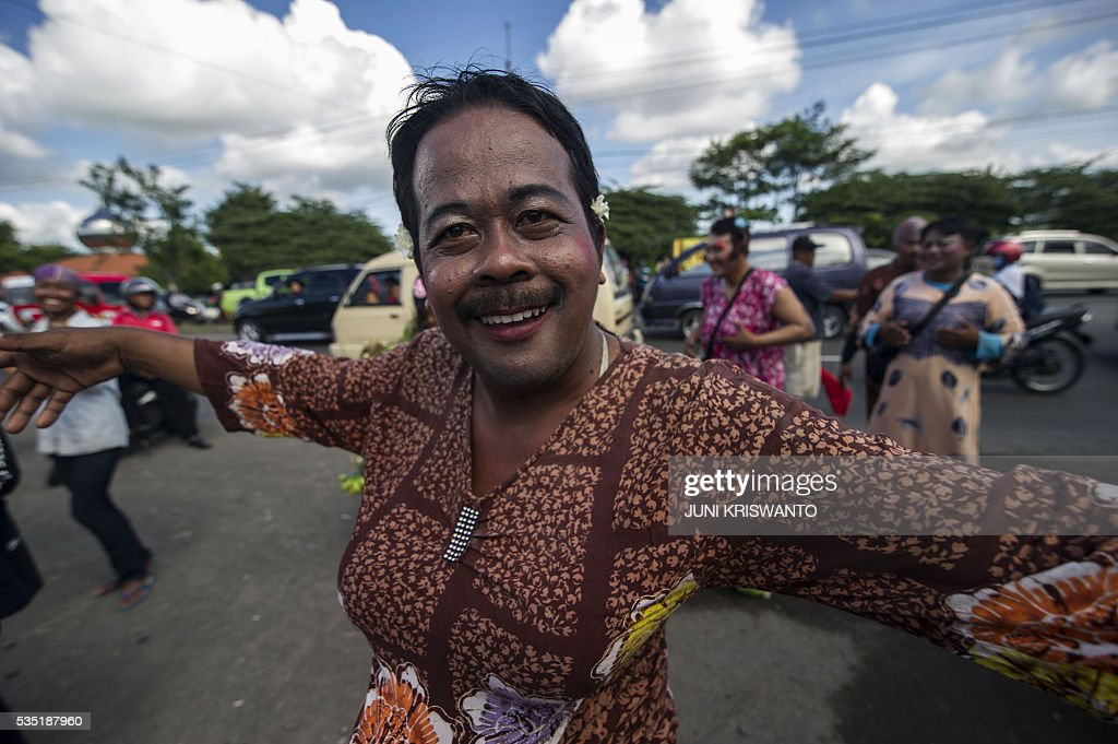 A survivor dressed as a woman, to show his support for the women who lost their livelihoods, takes part in a parade to mark the 10th anniversary of the mudflow disaster that buried villages, factories, shops and even a major highway in the Sidoarjo district of Java island on May 29, 2016. Independent studies alternate blame between oil and gas company PT Lapindo Brantas, which was drilling in the area at the time, and an earthquake that struck two days earlier about 260 kilometres (162 miles) away. / AFP / JUNI
