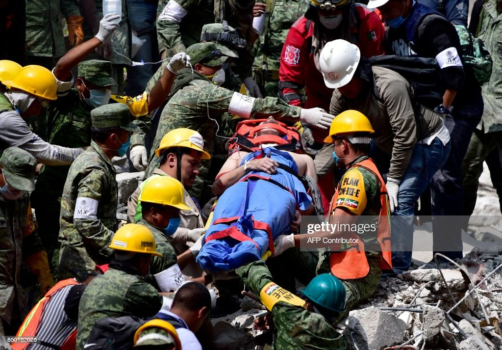 A survivor is pulled out of the rubble from a flattened building in Mexico City on September 20, 2017 as the search for survivors continues a day after a strong quake hit central Mexico. A powerful 7.1 earthquake shook Mexico City on Tuesday, causing panic among the megalopolis' 20 million inhabitants on the 32nd anniversary of a devastating 1985 quake. / AFP PHOTO / Pedro PARDO