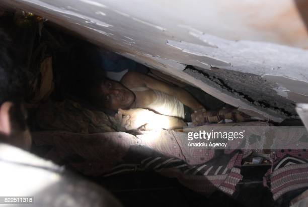 A survivor looks out of from the debris as he wait to be rescued at site of a collapsed building in Mumbai on July 25 2017 At least six people were...
