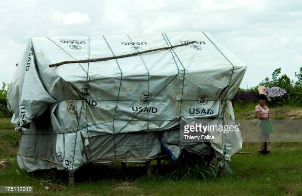 A survivor of cyclone Nargis stands beside a temporary house covered with a tarpaulin given by the USAID the United States government humanitarian...