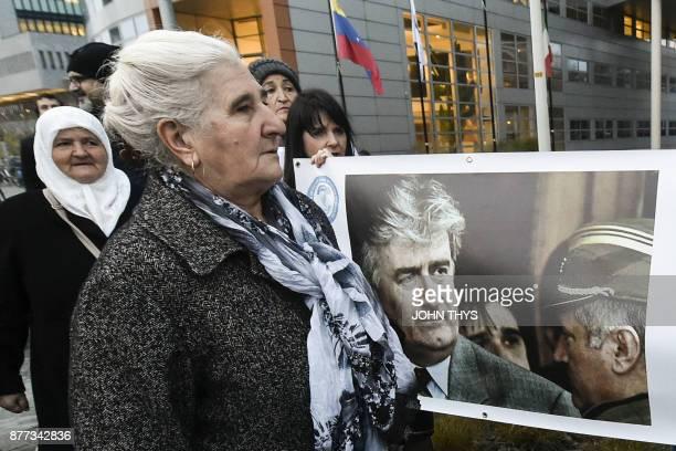 TOPSHOT Survivor of Srebrenica 1995 massacre and leader of women's Srebrenica survivors movement Munira Subasic walks past protestors as she arrives...