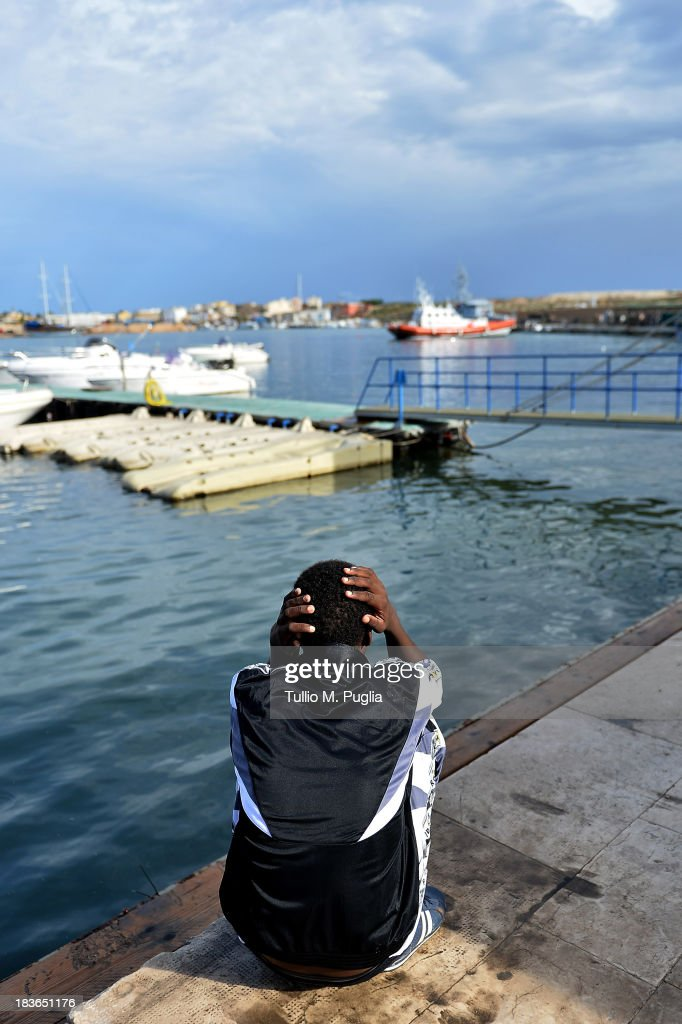 A survivor of the shipwreck of immigrants off the Italian coast looks out over the water of Lampedusa on October 8, 2013 in Lampedusa, Italy. The search for bodies continues off the coast of Southern Italy as the death toll of African migrants who drowned as they tried to reach the island of Lampedusa is expected to reach over 300 people. The tragedy has bought fresh questions over the thousands of asylum seekers that arrive into Europe by boat each year.