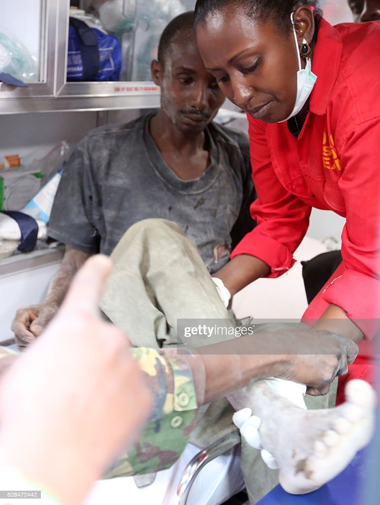 A survivor pulled alive from the rubble of an apartment block after it collapsed six days ago in Kenya's capital, is treated by medical staff on May 5 in Nairobi. Located in the poor, tightly-packed Huruma neighbourhood, the building, which housed around 150 families crammed into single rooms, had been slated for demolition after being declared structurally unsound. Several buildings have collapsed in recent years in Nairobi and other Kenyan cities, where a property boom has seen buildings shoot up at speed, often with scant regard for regulations. / AFP / -