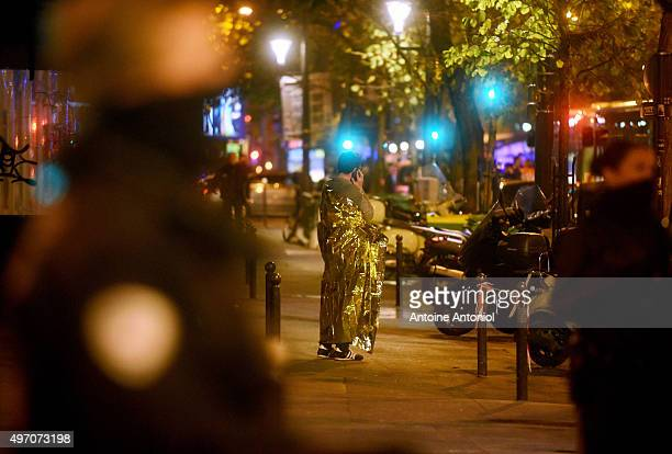 A survivor talks on his phone after gunfire in the Bataclan concert hall on November 13 2015 in Paris France According to reports over 150 people...