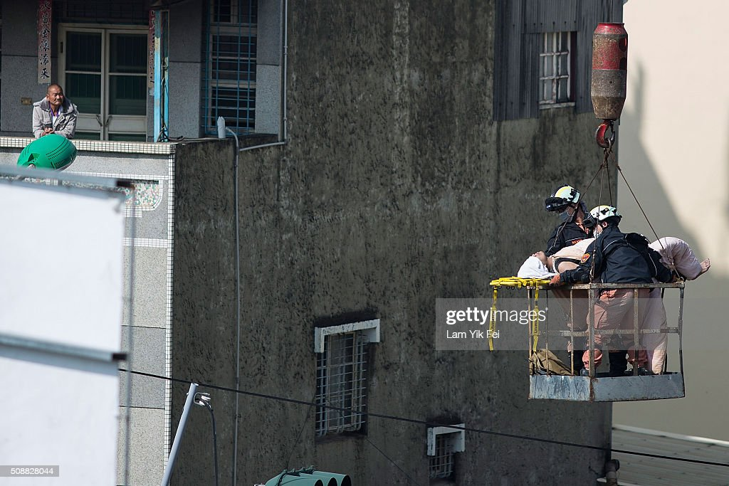A survivor transported by rescue workers at a collapsed building on February 7, 2016 in Tainan, Taiwan. A magnitude 6.4 earthquake hit southern Taiwan early Saturday, toppling several buildings, killing at least fourteen people, and leaving over one hundred missing in Tainan.