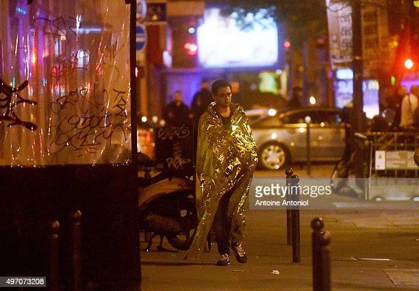 A survivor walks in the street after gunfire in the Bataclan concert hall on November 13 2015 in Paris France According to reports over 150 people...