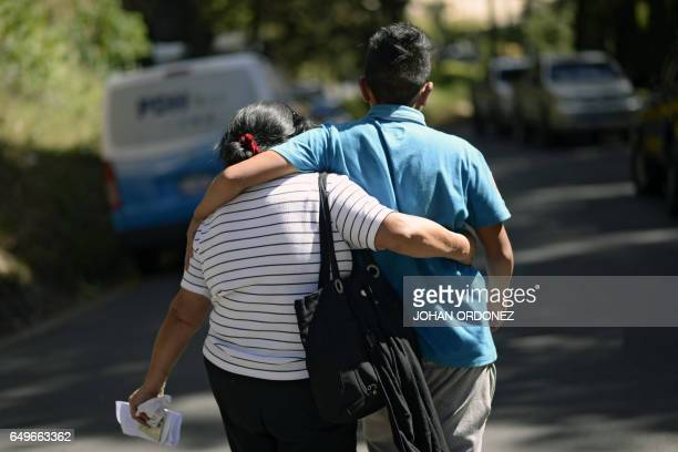 A survivor walks with a relative outside the children's shelter Virgen de la Asuncion after a fire at the facility killed at least 19 people in San...