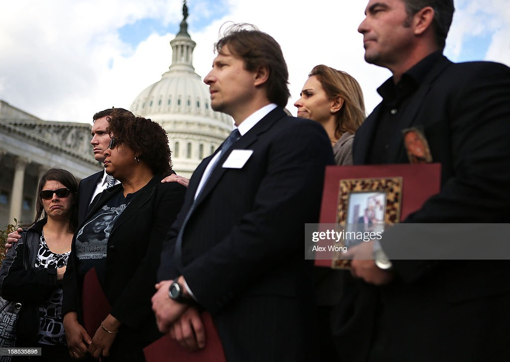 Survivors and family members of victims of gun violence, Jessica Watts of Aurora, Colorado, who lost her cousin Jonathan Blunk in the movie theater shooting, Colin Goddard, who was shot multiple times at the Virginia Tech shooting, local resident Nardyne Jefferies, who lost her daughter in a drive-by shooting by an AK-47-style assault rifle, Andrei Nikitchyuk of Newtown, Connecticut, whose son was in the building when the Sandy Hook Elementary School shooting happened, and Paul Wilson (R) of Seal Beach, California, who lost his wife Christy in a shooting at a hair salon, listen during a news conference at the House Triangle on Capitol Hill December 18, 2012 in Washington, DC. U.S. Rep. David Cicilline (D-RI) held a news conference with the Brady Campaign to discuss gun violence.