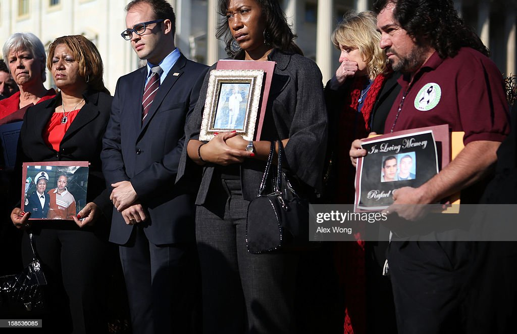Survivors and family members of victims of gun violence listen during a news conference at the House Triangle on Capitol Hill December 18, 2012 in Washington, DC. U.S. Rep. David Cicilline (D-RI) held a news conference with the Brady Campaign to discuss gun violence.