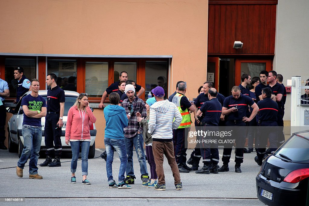 Survivors and relatives discuss on April 16, 2013 in front of the firefighters building in Bourg d'Oisan, where survivors of a coach crash have been sheltered. At least one person died and three others were seriously injured after a coach carrying Britons crashed in the French Alps, local officials said. The coach slammed into the mountain face bordering the winding road down from the popular ski resort of Alpe d'Huez and caught fire. An official told AFP one person -- thought to be the bus driver -- died, three others were seriously injured and 21 more slightly hurt. Police had previously said three perished in the accident.