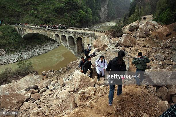 Survivors and rescuers make their way along a damaged road after an earthquake hit Lushan County in Ya'an City southwest China's Sichuan province on...