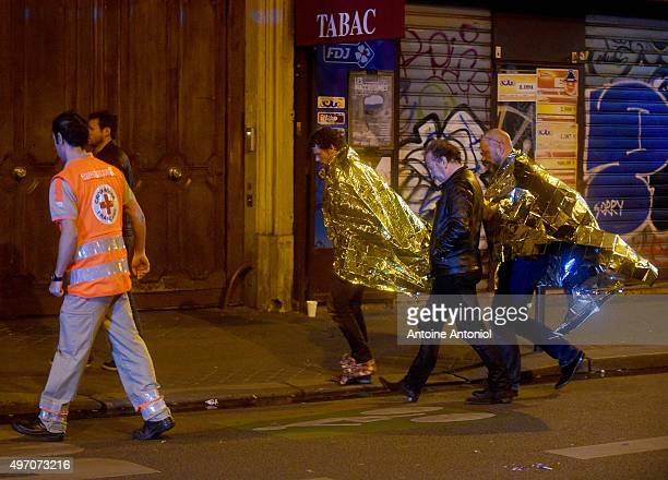 Survivors are escorted away after gunfire in the Bataclan concert hall on November 13 2015 in Paris France According to reports over 150 people were...