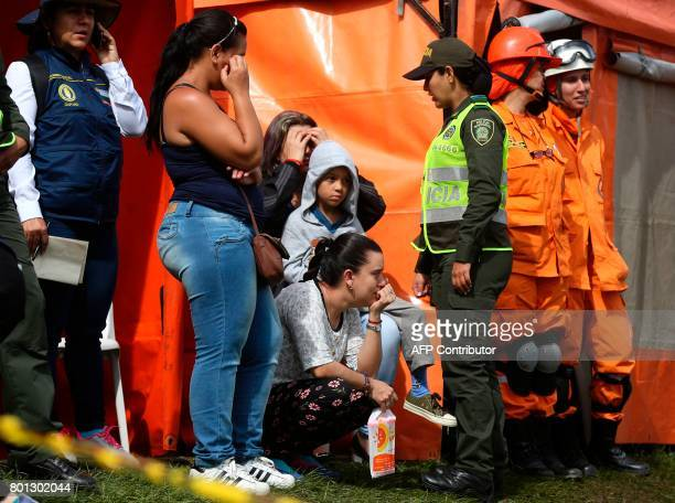 Survivors are pictured next to rescue team members and police officers after the tourist boat 'Almirante' sank in the Reservoir of Penol in Guatape...
