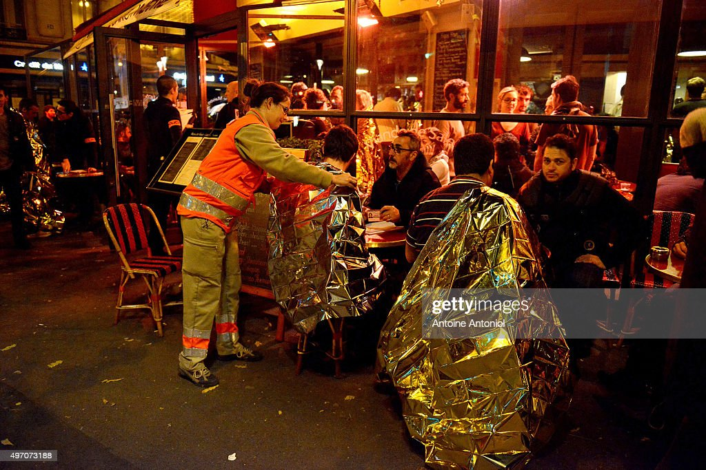 Survivors are tended to at a cafe after gunfire in the Bataclan concert hall on November 13 2015 in Paris France According to reports over 150 people...