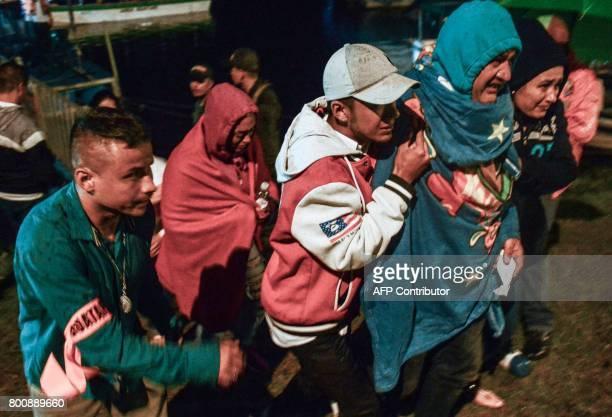 CORRECTION Survivors clad in blankets arrive onshore after being rescued from the tourist boat Almirante in the Reservoir of Penol in Guatape...