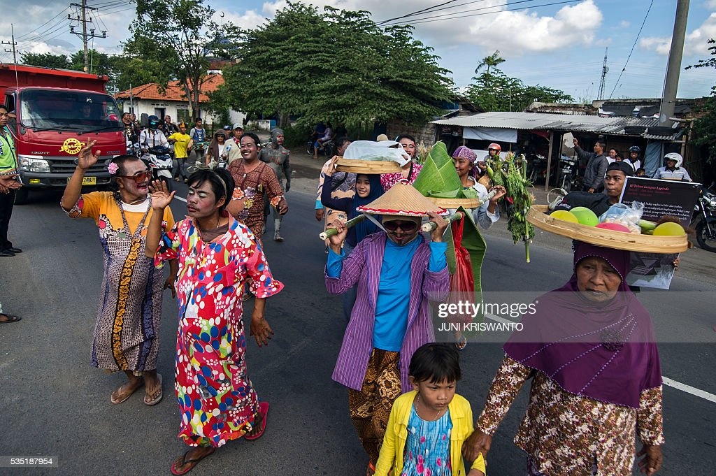 Survivors dressed as women, to show their support for the women who lost their livelihoods, take part in a parade to mark the 10th anniversary of the mudflow disaster that buried villages, factories, shops and even a major highway in the Sidoarjo district of Java island on May 29, 2016. Independent studies alternate blame between oil and gas company PT Lapindo Brantas, which was drilling in the area at the time, and an earthquake that struck two days earlier about 260 kilometres (162 miles) away. / AFP / JUNI