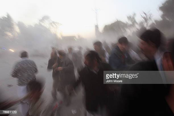 Survivors flee a bomb blast attack on former Prime Minister Benazir Bhutto on December 27 2007 following a campaign rally in Rawalpindi Pakistan The...