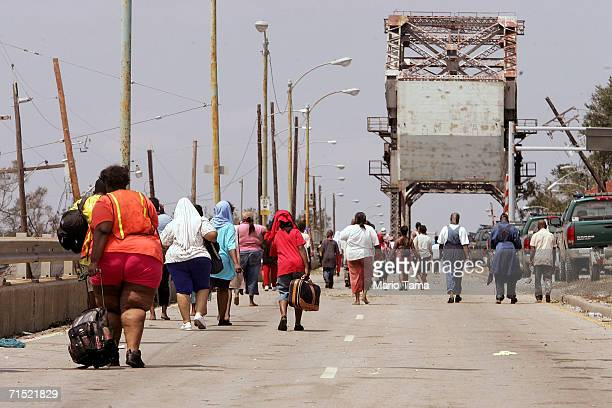 Survivors from the Lower Ninth Ward walk to a bridge crossing the Industrial Canal after being rescued by boat from their homes during the aftermath...