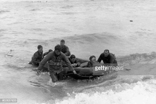 Survivors of a sunken LCVP arrive safely ashore in a rubber life raft at Omaha Beach on June 6 1944 during the Normandy landing France / AFP PHOTO /