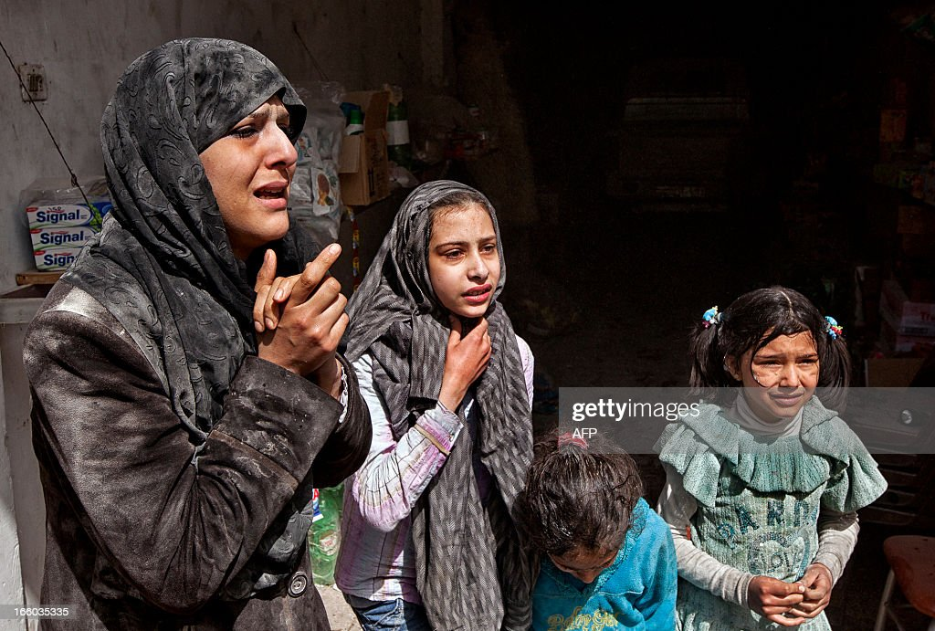 Survivors of an air strike by government forces that according to eyewitnesses destroyed two five-storey apartment blocks and severely damaged ten buildings in a residential neighbourhood of the northern Syrian city of Aleppo, look in shock at the scene of the attack as local residents try to rescue those trapped under the rubble on April 7, 2013. Warplanes also raided Yabrud near Damascus and Qusayr in the central province of Homs, as tanks shelled rebel enclaves in Homs city.