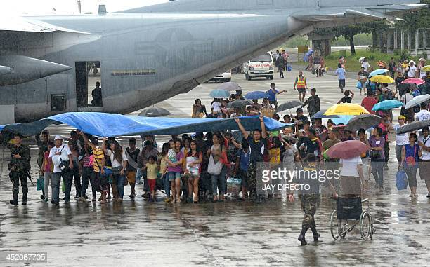 Survivors of Super Typhoon Haiyan that hit the central Philippines walk on the tarmac after disembarking from a Philippine Air Force military cargo...