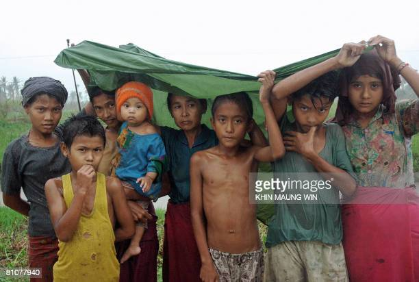 Survivors of the cyclone Nargis stand under the rain in Bogalay on May 13 2008 The United Nations warned on May 13 that Myanmar faced a 'second...