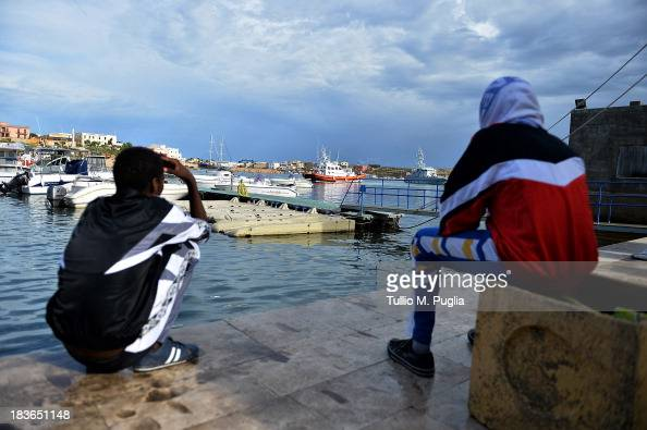 Survivors of the shipwreck of immigrants off the Italian coast sit near the water of Lampedusa on October 8 2013 in Lampedusa Italy The search for...