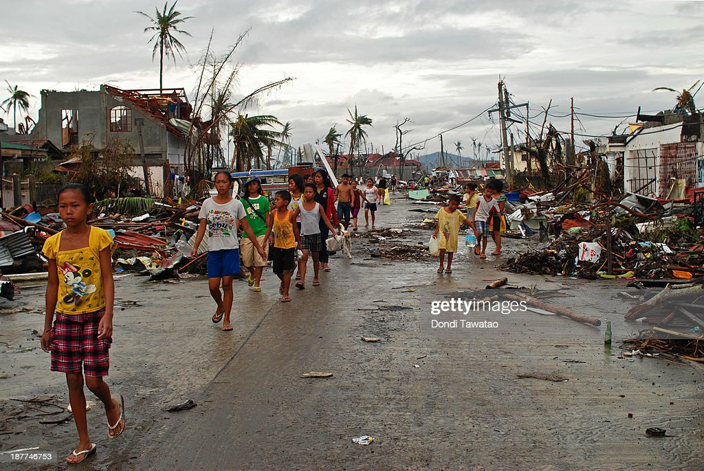 Survivors of the typhoon walk through a devastated area on November 12 2013 in Leyte Philippines Four days after the typhoon devastated the region...