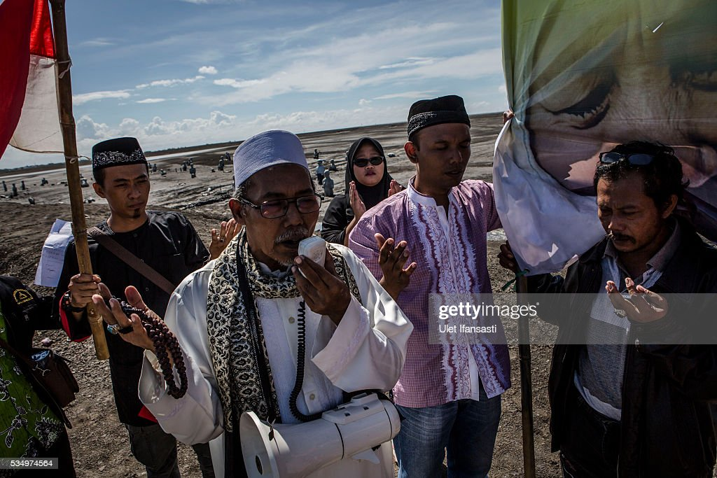 Survivors pray at mudflow areas to mark 10 years after indonesia's Sidoarjo mudflow on May 27, 2016 in Sidoarjo, East Java, Indonesia. Residents of villages that were damaged by the Sidoarjo mudflow and residents received compensation, after almost ten years, from the Indonesian oil and gas company, PT Lapindo Brantas. The mudflow eruption is suspected to have been triggered by the drilling activities of oil and gas company, though they refute the claims, instead blaming a 6.3 magnitude earthquake that struck a neighboring city two days before the mudflow eruption. The earthquake struck Yogyakarta on May 27th, 2006, a city 150 miles west of a drill site in Sidoarjo, two days before the mudflow eruption. According to reports, twenty lives were lost and nearly 40,000 people displaced, with damages topping $2.7 billion. Ten years since the eruption, the mud geysers continue to spurt daily and high levels of heavy metals have been detected in nearby rivers.