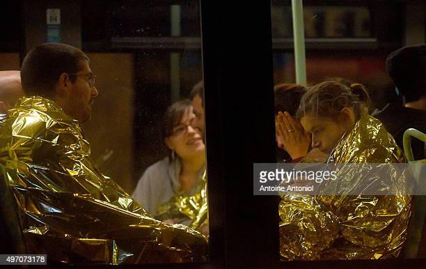 Survivors sit on a bus after gunfire in the Bataclan concert hall on November 13 2015 in Paris France According to reports over 150 people were...