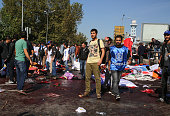Survivors stand amongst the dead and injured at the blast scene after an explosion during a peace march in Ankara October 10 2015 Turkey Turkish...
