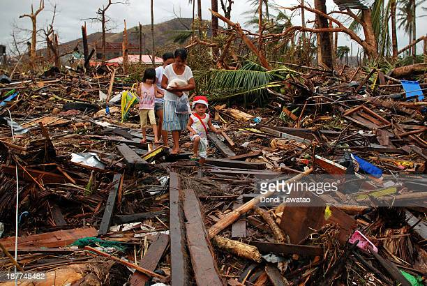 Survivors walk over debris as they pass through an area devasted by Typhoon Haiyan on November 12 2013 in Leyte Philippines Four days after the...
