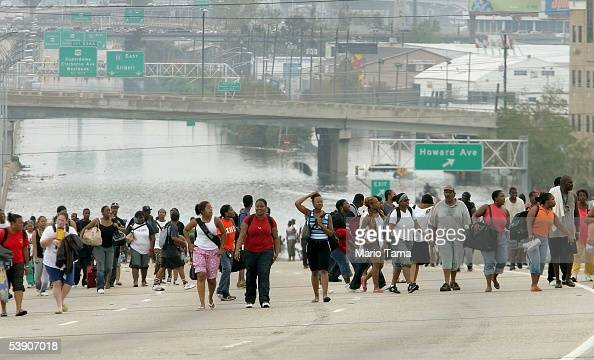 Survivors walk to high ground after being evacuated from high water to a highway September 1 2005 in New Orleans Louisiana Rescue efforts continue as...