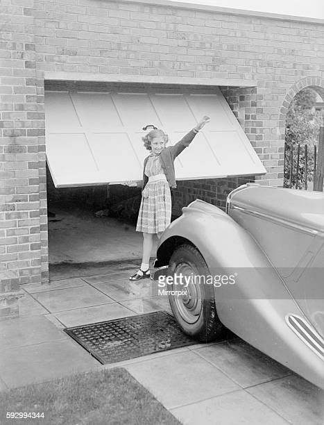 Susan Davies seen here opening the garage door for her father and his car 28th September 1952