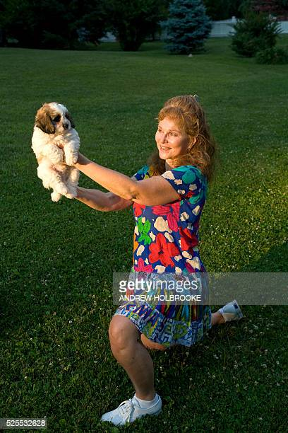 Susan Keith lovingly holds up her new pet a puppy named 'Rhymer' The dog a Cockabichon is a popular hybrid a crossbreed of a Cocker Spaniel and a...