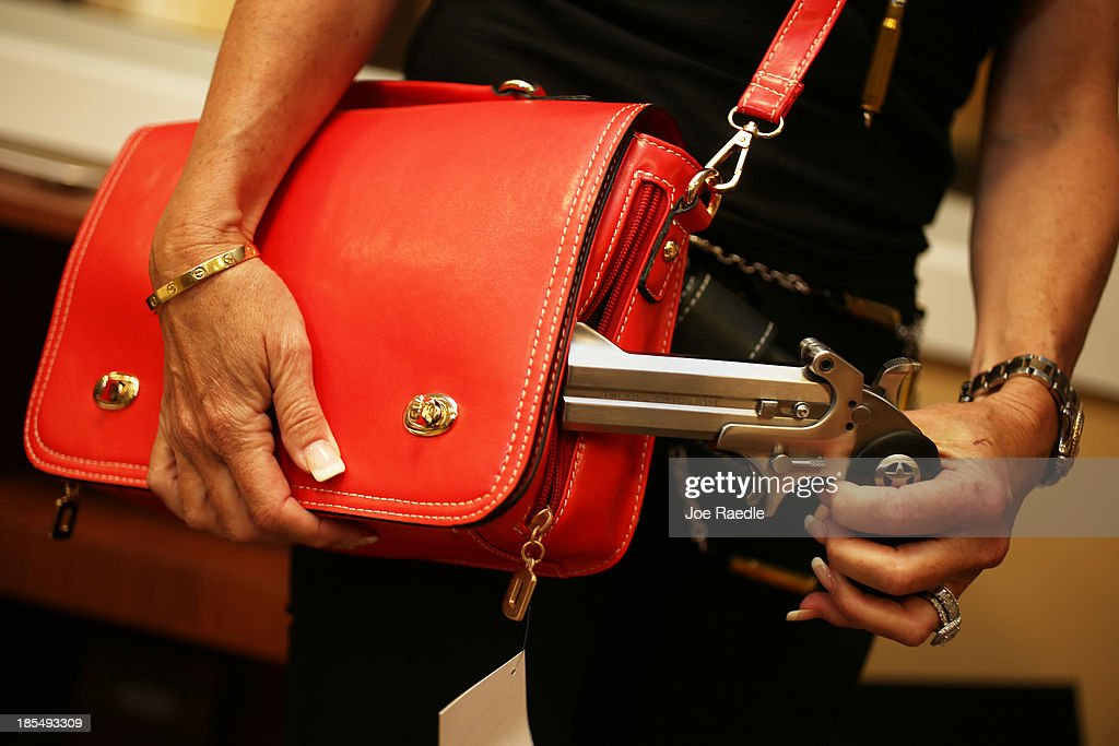 Susan Kushlin poses with a concealed-carry handbag that her company, Gun Girls, Inc., created for women that enjoy guns on October 21, 2013 in Boca Raton, Florida. Her line includes bullet jewelry, handbags, belts and custom logo apparel with some of the items priced at $35 gold-toned bullet belts, $20 dangling gun earrings, $76 pink concealed-carry handbags and $21 rhinestone-studded tank tops.