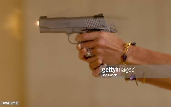 Susan Kushlin shoots a pistol while wearing one of the bracelets that her company Gun Girls Inc created for women that enjoy guns on October 21 2013...