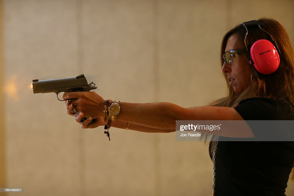 Susan Kushlin shoots a pistol while wearing one of the bracelets that her company, Gun Girls, Inc., created for women that enjoy guns on October 21, 2013 in Boca Raton, Florida. Her line includes bullet jewelry, handbags, belts and custom logo apparel with some of the items priced at $35 gold-toned bullet belts, $20 dangling gun earrings, $76 pink concealed-carry handbags and $21 rhinestone-studded tank tops.