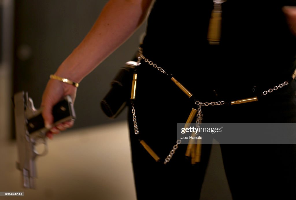 Susan Kushlin wears a chain belt that her company, Gun Girls, Inc., created for women that enjoy guns on October 21, 2013 in Boca Raton, Florida. Her line includes bullet jewelry, handbags, belts and custom logo apparel with some of the items priced at $35 gold-toned bullet belts, $20 dangling gun earrings, $76 pink concealed-carry handbags and $21 rhinestone-studded tank tops.