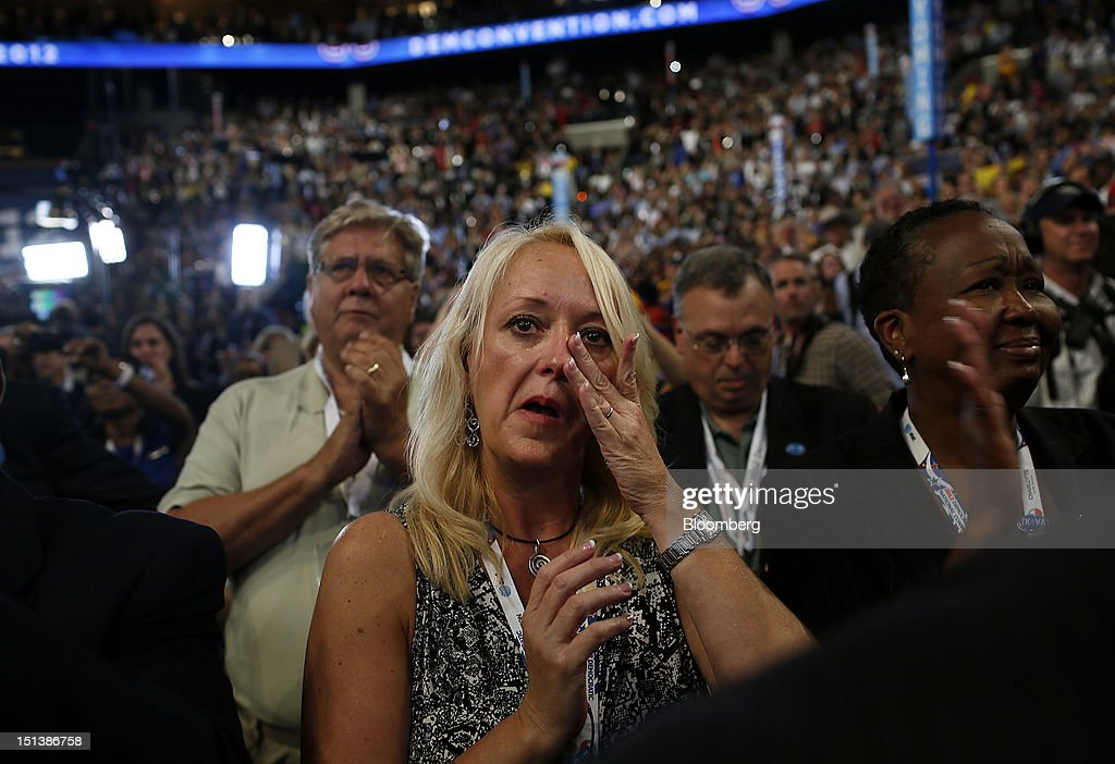 Susan Rowland, a delegate from Virginia, center, wipes away a tear while former Arizona congresswoman Gabrielle Giffords, unseen, recites the Pledge of Allegiance during day three of the Democratic National Convention (DNC) in Charlotte, North Carolina, U.S., on Thursday, Sept. 6, 2012. President Barack Obama's prime-time nomination acceptance speech tonight at the DNC will be aimed at convincing voters that a slow economic recovery will accelerate if they give him a second term. Photographer: Victor J. Blue/Bloomberg via Getty Images