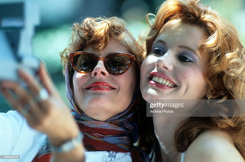 Susan Sarandon and Geena Davis taking Polaroid of themselves in a scene from the film 'Thelma & Louise', 1991.