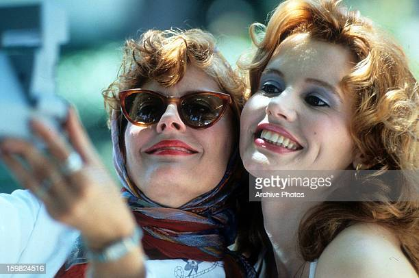 Susan Sarandon and Geena Davis taking Polaroid of themselves in a scene from the film 'Thelma Louise' 1991