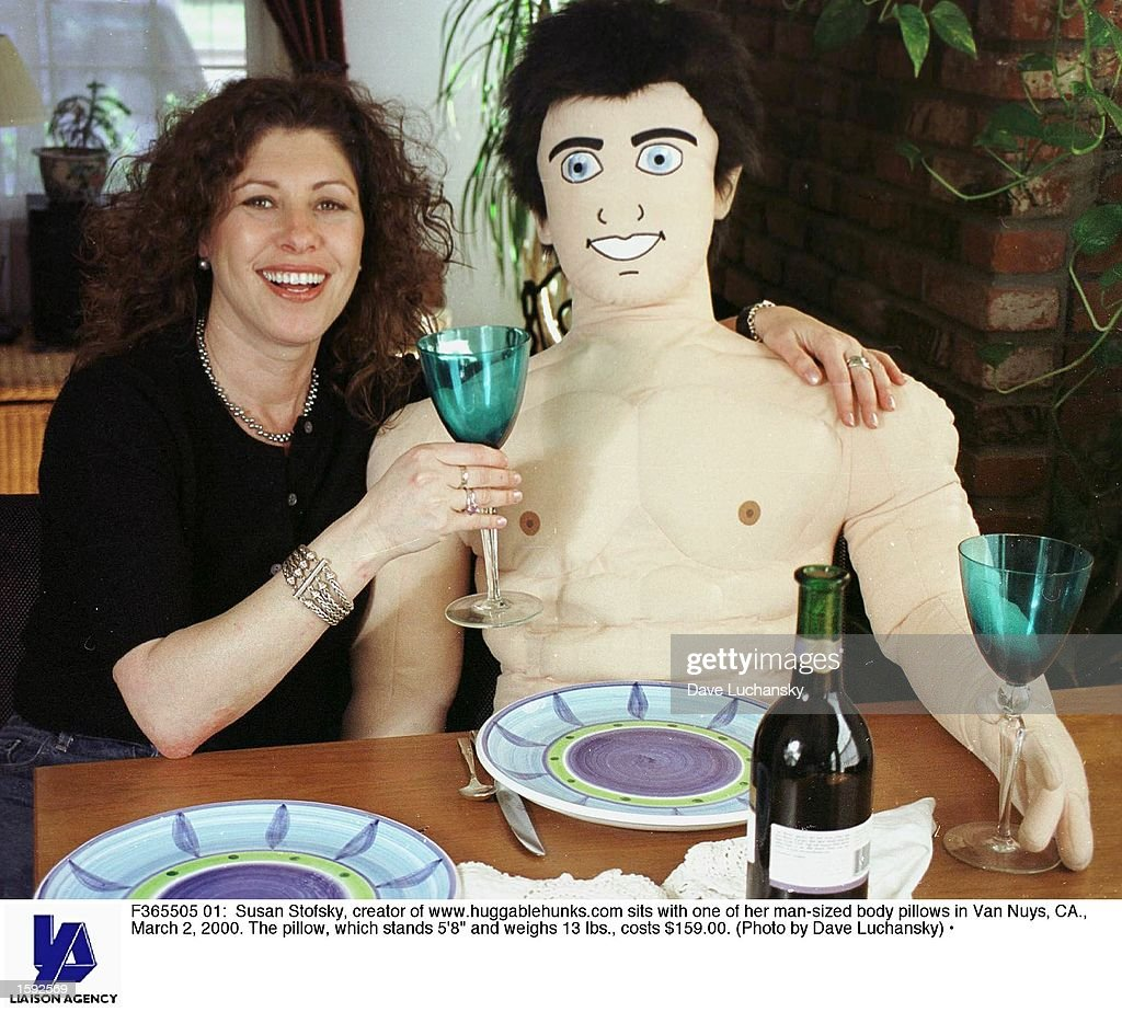 Susan Stofsky, creator of www.huggablehunks.com sits with one of her man-sized body pillows in Van Nuys, CA., March 2, 2000. The pillow, which stands 5''8' and weighs 13 lbs., costs $159.00.